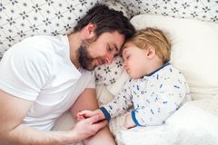 Father holding hand of a sleeping toddler boy in bed at home. Father holding hand of a sleeping toddler boy lying in bed at home. Paternity leave Royalty Free Stock Photography