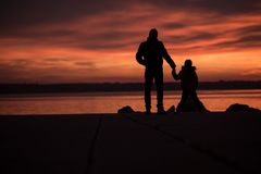 Father holding hands with his son. As they stand silhouetted against a colorful vivid orange ocean sunset stock photography