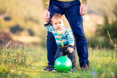 Father holding hands of his son making first steps Stock Photo