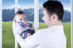 Father holding his attractive baby Stock Images