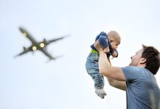 Father holding his baby. (airplane on background Stock Images