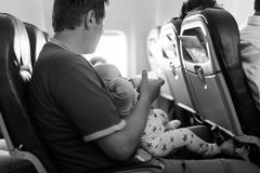 Father holding his baby daughter during flight on airplane going on vacations Stock Image