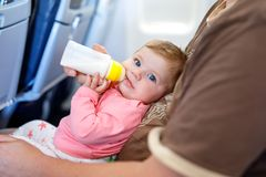 Father holding his baby daughter during flight on airplane going on vacations. Father holding baby daughter during flight on airplane going on vacations. Baby Royalty Free Stock Photo