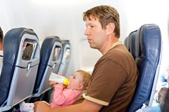 Father holding his baby daughter during flight on airplane going on vacations royalty free stock photos