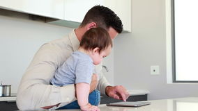 Father holding his baby before work and using tablet. At home in the kitchen stock footage