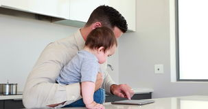 Father holding his baby before work and using tablet. At home in the kitchen stock video