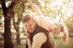 Father holding his daughter on shoulders and playing to. Cheerful father holding his daughter on shoulders and playing together stock images