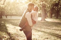 Father holding his little girl in arms and plying in park. royalty free stock images