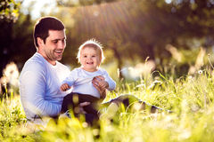 Father holding his little son, sitting on the grass Stock Image