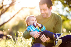 Father holding his little son, sitting on the grass Royalty Free Stock Photo