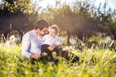 Father holding his little son, sitting on the grass Royalty Free Stock Images