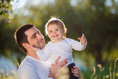 Father holding his little son, sitting on the grass Royalty Free Stock Image