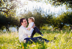 Father holding his little son, sitting on the grass Stock Images