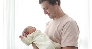 Father holding his newborn baby daughter. Proud father holding his newborn baby daughter in his at home stock footage