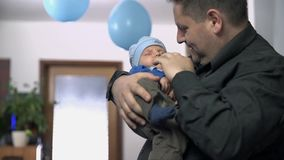 Father holding his newborn baby. Proud father playing with newborn son at home, celebrating offspring. Slow motion footage stock footage