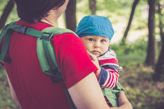 Father holding his son in baby carrier walking in the park. Warm vintage filter used royalty free stock photography
