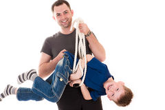Father holding his son caught in the rope Stock Photo
