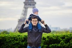 Father holding his son on shoulders near the Eiffel tower. Father holding his little son on his shoulders near the Eiffel tower in Paris. Happy family of two royalty free stock photos