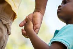 Father holding his his sons hand. African American loving father guiding his son Royalty Free Stock Images