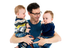 Father is holding his twin sons in his arms. Proud Father is holding his twin sons in his arms. A single parent is carrying his twins and smiling. Isolated on stock image