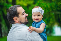 Father holding his young daughter in the park. stock photography