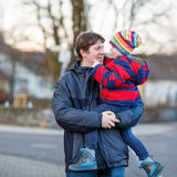 Father holding kid boy, son on arm outdoors. Active father holding his child, little funny kid boy on arm, on cold day. Man and boy walking together in a park in Stock Photos