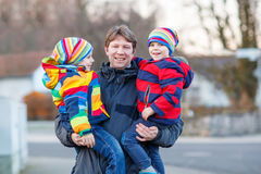 Father holding kid boys, sons on arm outdoors Stock Image