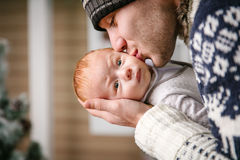 Father holding and kissing baby son among while wearing winter hat Stock Photos