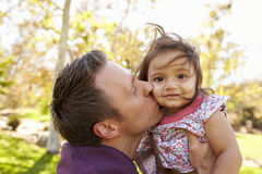 Father holding and kissing his young daughter in a park Stock Photos