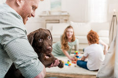 Father holding labrador retriever puppy, happy family behind at home royalty free stock photos
