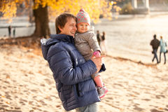 Father holding little daughter on hands at beach Stock Photography