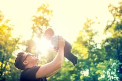 Father holding little kid in arms, throwing baby in air. concept of happy family, vintage effect against light. Happy father holding little kid in arms, throwing stock photo