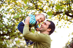 Father holding little son, throwing him in the air Stock Photos