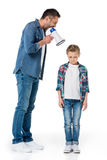Father holding megaphone and screaming at little son standing Royalty Free Stock Photo
