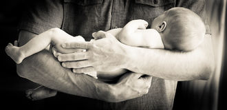 Father Holding Newborn Baby Boy. Cute newborn baby boy being held in his father's arms against a bare chest Royalty Free Stock Image