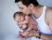 Father holding newborn baby kissing his head eyes closed stock photography