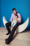 Father holding newborn baby in modern children's room interior Stock Images
