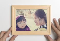 Father holding picture of mother a their child for family love concept. Father hand holding picture of mother a their child for family love concept Royalty Free Stock Photos