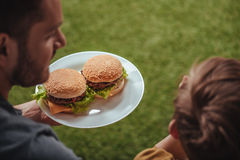 Father holding plate with homemade burgers with son Royalty Free Stock Photos