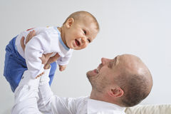 Father holding and playing with his infant son Royalty Free Stock Photo