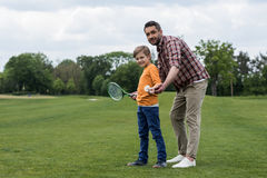 Father holding shuttlecock and teaching little son playing badminton Stock Photography