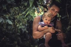 Father holding small baby daughter among lush foliage during tropical holidays with copy space. Father holding small baby daughter among lush foliage during Royalty Free Stock Photo