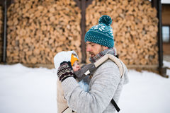 Father holding son in baby carrier. Winter nature. Stock Image