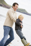Father holding son at beach. Smiling stock image