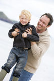 Father holding son at beach smiling.  stock photo