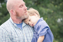 Father Holding Son. Bearded father with his eyes closed, holding his son in his arms outdoors in a green setting Royalty Free Stock Photography