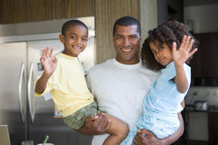 Father holding son and daughter (5-9) in kitchen, smiling, portrait stock image