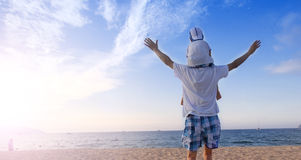 Father holding son on his shoulders at the beach. With blue sky Stock Photos