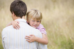 Father holding son outdoors smiling.  stock photos