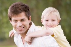 Father holding son outdoors smiling. At camera royalty free stock photo
